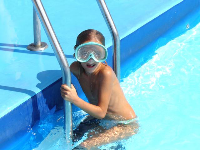 Odrostlejší dítě s potápěčskými brýlemi na hlavě vylézající z bazénu.jpg